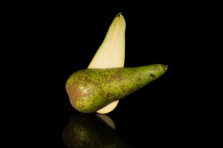 Group of two halves of fresh green pear conference isolated on black glass