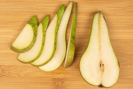 Group of one half five slices of fresh green pear flatlay on light wood