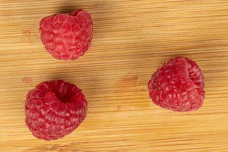 Group of three whole fresh red raspberry flatlay on light wood Stok Fotoğraf