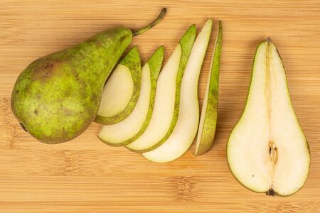 Group of one whole one half five slices of fresh green pear flatlay on light wood