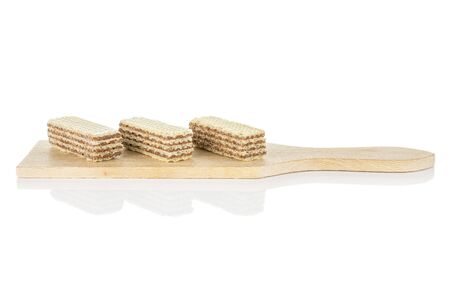 Group of three whole crispy beige hazelnut wafer cookie on small wooden cutting board isolated on white background