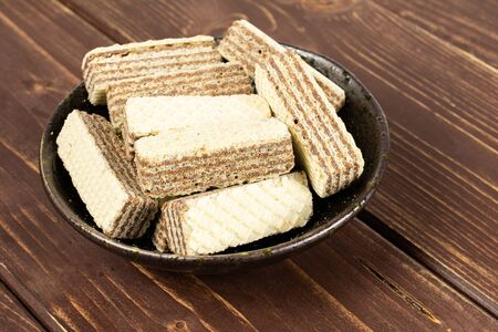 Lot of whole crispy beige hazelnut wafer cookie in dark ceramic bowl on brown wood