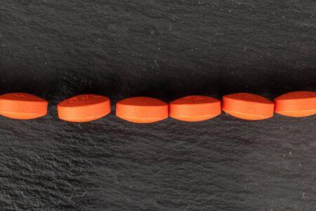 Group of six whole orange tablet pharmacy flatlay on grey stone