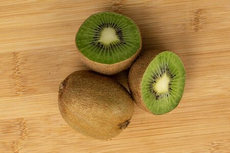 Group of one whole two halves of exotic brown kiwi flatlay on light wood