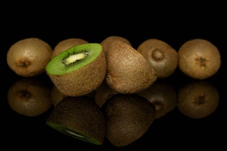 Group of five whole two halves of exotic brown kiwi isolated on black glass