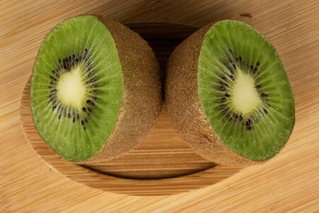 Group of two halves of exotic brown kiwi on round bamboo coaster flatlay on light wood