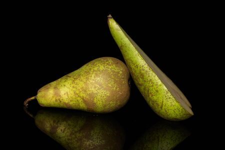 Group of one whole one half of fresh green pear conference isolated on black glass