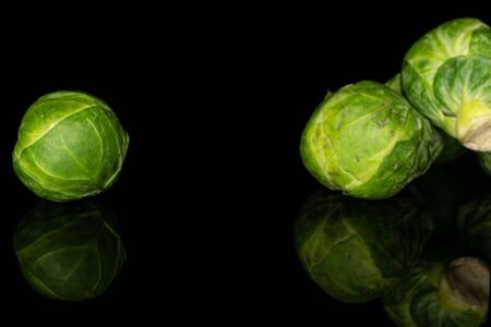 Group of three whole fresh green brussels sprout isolated on black glass