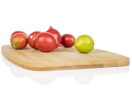 Lot of whole bright fresh tomato de barao on bamboo cutting board isolated on white background