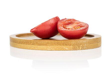 Group of two halves of fresh tomato de barao on round bamboo coaster isolated on white background