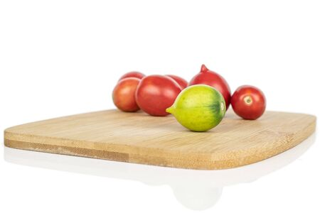 Lot of whole fresh tomato de barao on bamboo cutting board isolated on white background Banco de Imagens