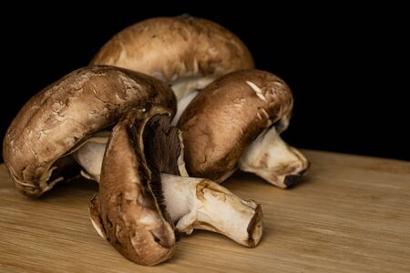 Group of four whole fresh brown mushroom champignon on bamboo cutting board isolated on black glass