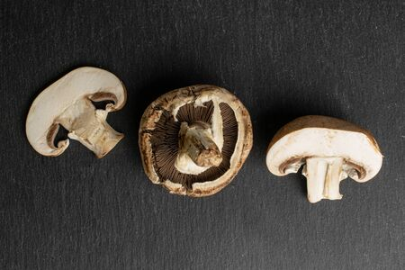 Group of one whole one half one slice of fresh brown mushroom champignon flatlay on grey stone Stok Fotoğraf