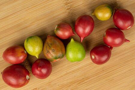Group of twelve whole fresh tomato de barao flatlay on light wood