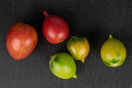 Group of five whole fresh tomato de barao flatlay on grey stone