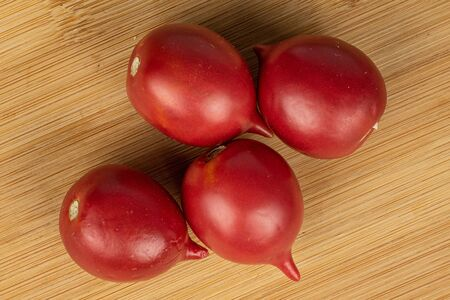 Group of four whole fresh tomato de barao flatlay on light wood
