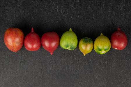Group of seven whole fresh tomato de barao flatlay on grey stone Zdjęcie Seryjne