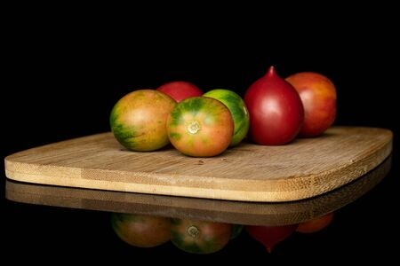 Group of six whole fresh tomato de barao on bamboo cutting board isolated on black glass Stok Fotoğraf