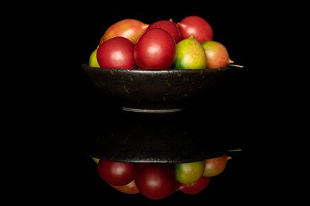 Lot of whole fresh tomato de barao on glazed bowl isolated on black glass 写真素材