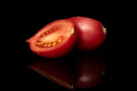 Group of two halves of fresh tomato de barao isolated on black glass