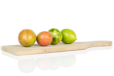 Group of four whole fresh tomato de barao on wooden cutting board isolated on white background
