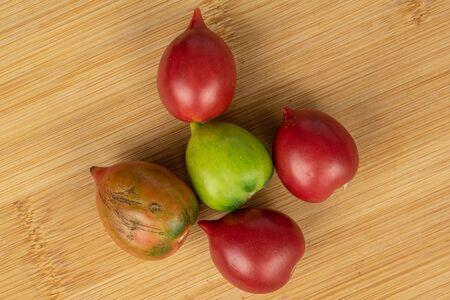 Group of five whole fresh tomato de barao flatlay on light wood