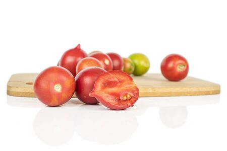 Lot of whole one half of fresh tomato de barao on bamboo cutting board isolated on white background