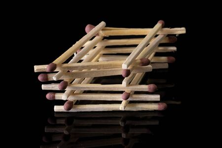 Lot of whole brown safety match tower isolated on black glass