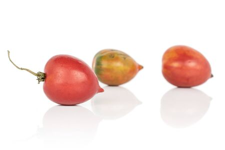 Group of three whole fresh tomato de barao one with stem isolated on white background