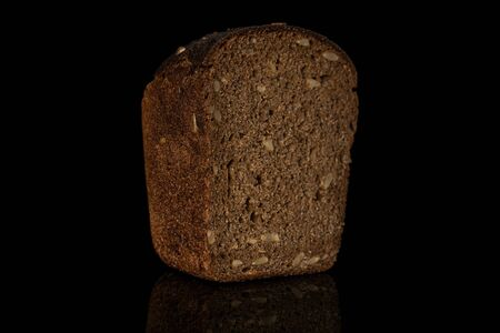 One half of fresh baked dark bread loaf isolated on black glass