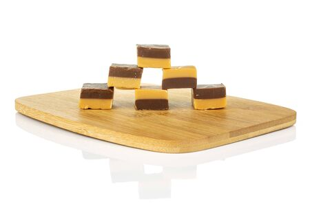 Group of six whole sweet brown caramel chocolate candy on bamboo cutting board isolated on white background