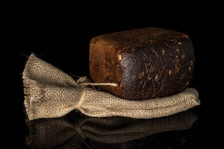 One whole fresh baked dark bread with jute bag isolated on black glass Archivio Fotografico