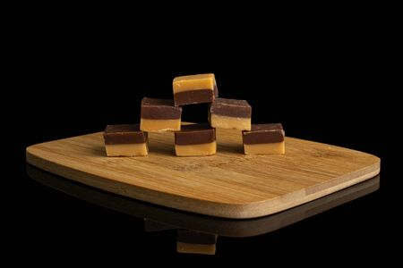 Group of six whole sweet brown caramel chocolate candy on bamboo cutting board isolated on black glass