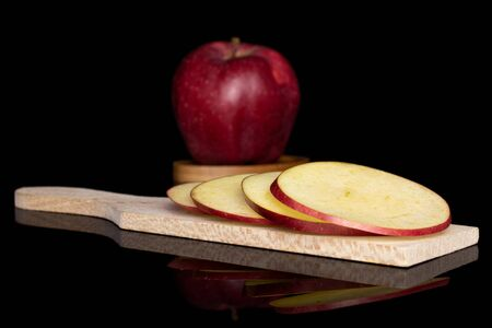Group of one whole four slices of fresh apple red delicious on wooden cutting board on round bamboo coaster isolated on black glass