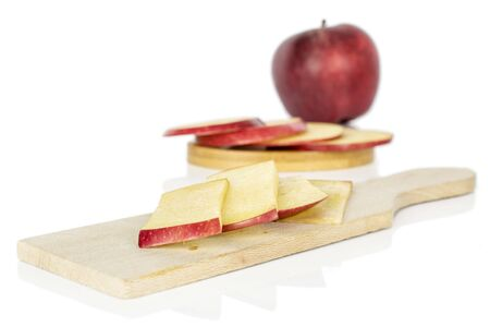 Group of one whole seven slices of fresh apple red delicious on round bamboo coaster on wooden cutting board isolated on white background