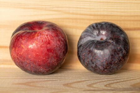 Group of two whole fresh red plum on natural wood