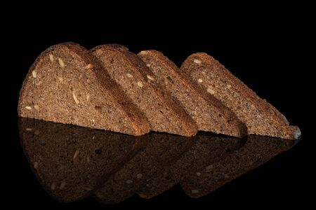 Group of four slices of fresh baked dark bread isolated on black glass