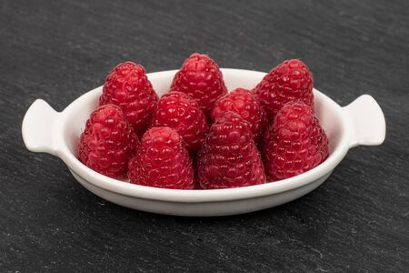 Group of nine whole fresh red raspberry in white oval ceramic bowl on grey stone