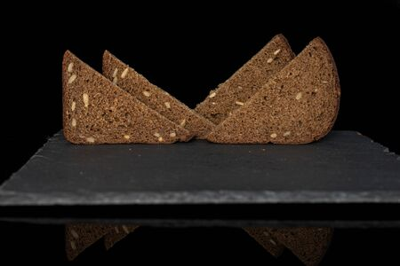 Group of four slices of fresh baked dark bread on grey stone isolated on black glass