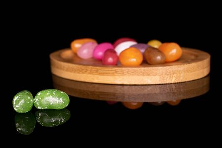 Lot of whole jelly bean candy green in focus on round bamboo coaster isolated on black glass Imagens