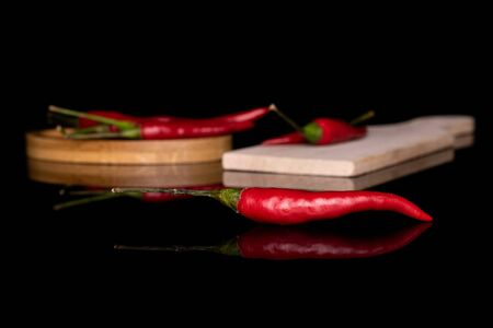 Group of six whole hot red chili on round bamboo coaster on wooden cutting board isolated on black glass