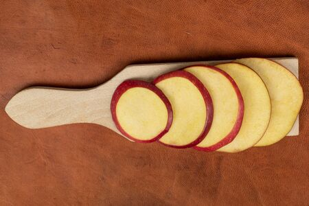 Group of five slices of fresh apple red delicious on wooden cutting board flatlay on cognac leather