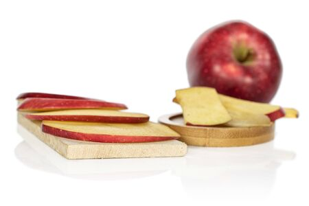 One whole lot of slices of fresh apple red delicious on wooden cutting board on round bamboo coaster isolated on white background Imagens
