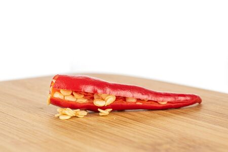 One half of hot red chili on bamboo cutting board isolated on white background