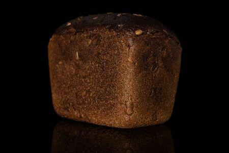 One whole fresh baked dark bread loaf isolated on black glass