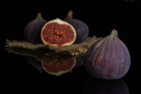 Group of three whole one half of fresh purple fig on natural sackcloth isolated on black glass