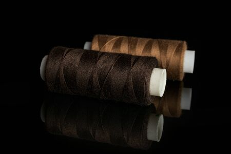 Group of two whole haberdashery item brown thread spools isolated on black glass Archivio Fotografico