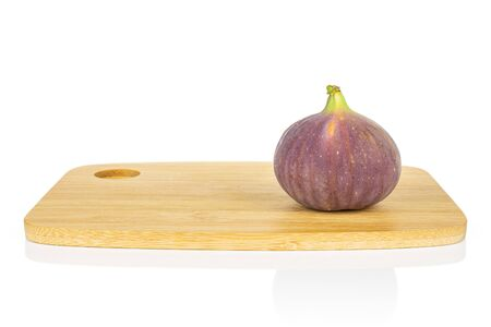 One whole fresh purple fig on bamboo cutting board isolated on white background