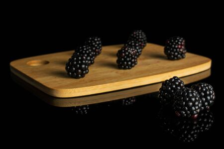 Group of ten whole fresh black blackberry on bamboo cutting board isolated on black glass Imagens