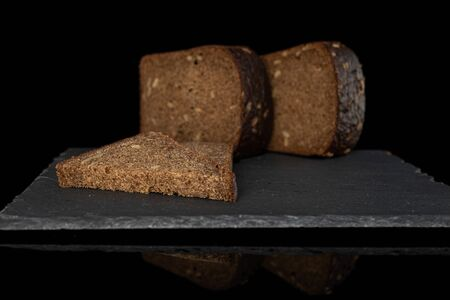 Group of two halves one slice of fresh baked dark bread on grey stone isolated on black glass